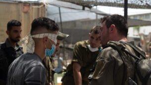 القوات الإسرائيلي تحقق مع شاب فلسطيني في إطار عمليات البحث عن الشخص المسؤول عن إلقاء طوبة على الجندي عميت بن يغال، والتي أسفرت عن مقتله، في قرية يعبد بالضفة الغربية، 13 مايو، 2020.(Israel Defense Forces)