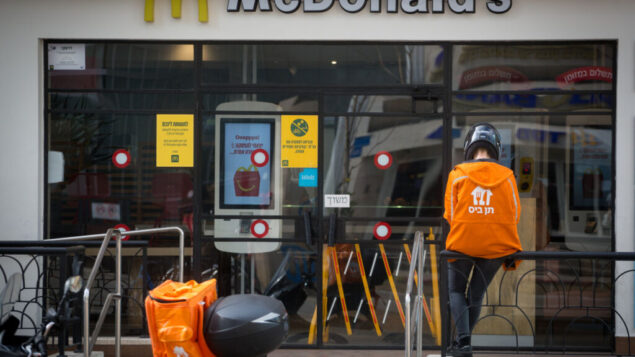 عامل توصيل طعام ينتظر خارج مطعم ماكدونالدز في تل أبيب، 18 أبريل 2020. (Miriam Alster / FLASH90)