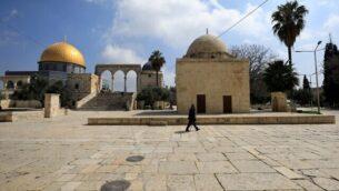 رجل يمر من امام قبة الصخرة في الحرم القدسي بالقدس القديمة، 16 مارس، 2020 (Emmanuel DUNAND/AFP)