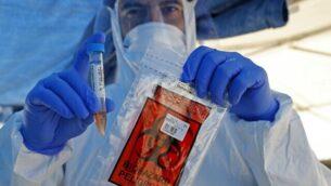 عامل طبي إسرائيلي يأخذ عينات في محطة 'افحص وسافر' لفحوصات كوفيد-19 في رمات هشارون قرب تل أبيب، 1 يونيو، 2020. (Jack Guez/AFP)