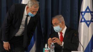 رئيس الوزراء بنيامين نتنياهو (يمين) يتحدث مع رئيس الوزراء البديل ووزير الدفاع بيني غانتس، وكلاهما يرتديان اقنعة وقائية بسبب جائحة كوفيد-19، خلال الاجتماع الأسبوعي للحكومة في القدس، 7 يونيو 2020. (Menahem KAHANA / AFP)
