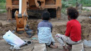 أطفال يمينون يشاهدون جرافة تقوم بحفر قبور في منطقة مخصصة لضحايا كوفيد-19، في مقبرة في تعز، ثالث أكبر مدينة في اليمن، 14 يونيو، 2020.( Ahmad AL-BASHA / AFP)