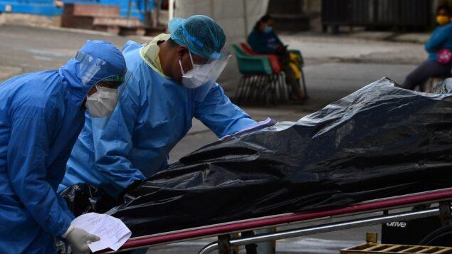 عاملون صحيون يحملون جثة ضحية كوفيد-19 على عربة خارج خيمة مرتجلة تم تركيبها في مستشفى إسكويلا الحكومي في تيغوسيغالبا، هندوراس، 15 يونيو 2020 (ORLANDO SIERRA / AFP)
