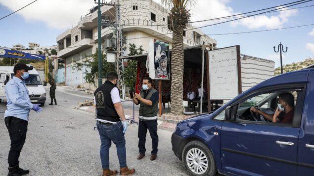 قوات الأمن الفلسطينية تقف عند نقطة تفتيش في قرية تفوح، غرب الخليل في الضفة الغربية، 19 يونيو 2020 (HAZEM BADER / AFP)