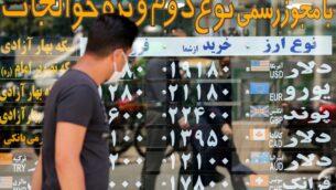 رجل يرتدي قناعًا بسبب فيروس كورونا يتحقق من أسعار صرف العملات وهو يمشي في العاصمة الإيرانية طهران، 22 يونيو 2020 (ATTA KENARE / AFP)