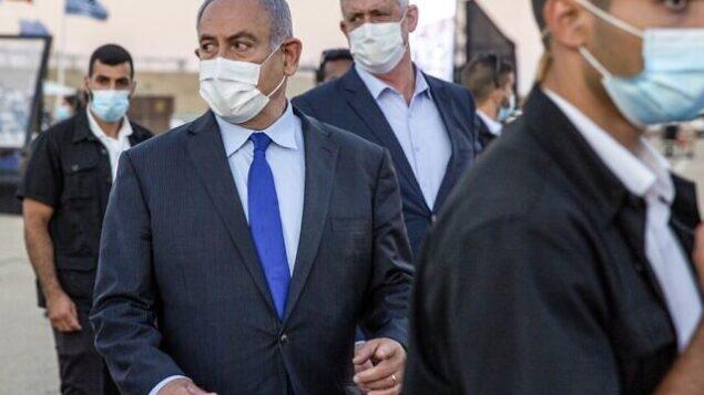 رئيس الوزراء بنيامين نتنياهو (وسط-يسار) وشريكه في الإئتلاف الحكومي، وزير الدفاع بيني غانتس (وسط-يمين)، يحضران حفل تخرج الطيارين الجدد في قاعدة 'حتساريم' الجوية بالقرب من بئر السبع، في 25 يونيو 2020. (Ariel Schalit / POOL / AFP)