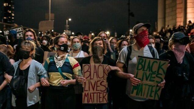 متظاهرون يحتجون على عنف الشرطة والعنصرية النظامية محصورون على جسر مانهاتن من قبل الشرطة لساعات خلال حظر التجول في مدينة نيويورك. تأتي أيام الاحتجاج، التي تكون عنيفة في بعض الأحيان، في العديد من المدن في جميع أنحاء البلاد، ردا على مقتل جورج فلويد أثناء وجوده في حجز الشرطة في مينيابوليس، مينيسوتا في 25 مايو. (Scott Heins/Getty Images/AFP)