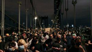 متظاهرون يحتجون على عنف الشرطة والعنصرية النظامية محصورون على جسر مانهاتن من قبل الشرطة لساعات خلال حظر التجول في مدينة نيويورك، 2 يونيو 2020 (Scott Heins/Getty Images/AFP)