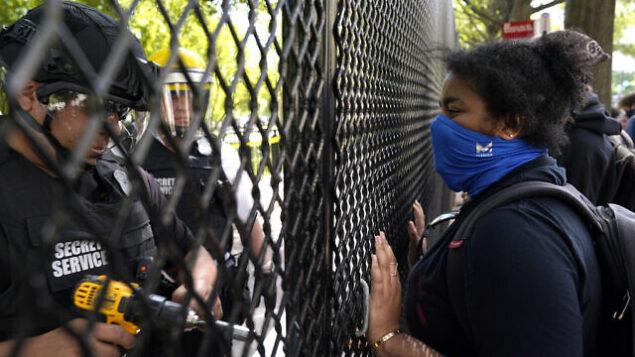 متظاهرة تراقب بينما تعمل شرطة الخدمة السرية الأمريكية على سياج يسد حديقة لافايت بينما تستمر الاحتجاجات على وفاة جورج فلويد، 2 يونيو 2020، بالقرب من البيت الأبيض في واشنطن. (AP Photo/Evan Vucci)