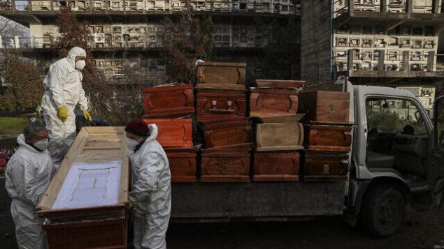 عمال يجمعون توابيت أشخاص تم حرق رفاتهم مؤخرًا وسط جائحة فيروس كورونا، في مقبرة لا ريكوليتا في سانتياغو، تشيلي، 28 يونيو 2020. (AP Photo / Esteban Felix)