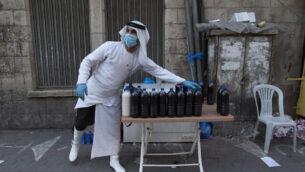 بائع فلسطيني يضع قناعا ويعرض عصير فاكهة طازج في الشارع في الوقت الذي لا تزال فيه الأسواق مغلقة جزئيا، في إطار إجراءات الإغلاق والحجر الصحي التي تم اتخاذها لحماية السكان من فيروس كورونا، في مدينة رام الله بالضفة الغربية، 19 مايو، 2020. (Nasser Nasser/AP)