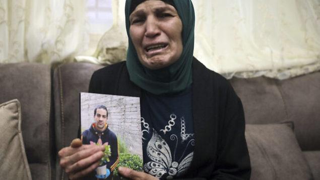 رنا الحلاق، والدة إياد الحلاق (32 عاما)، تحمل صورته في منزلها في وادي الجوز بالقدس الشرقية، 30 مايو، 2020. (AP Photo/Mahmoud Illean)