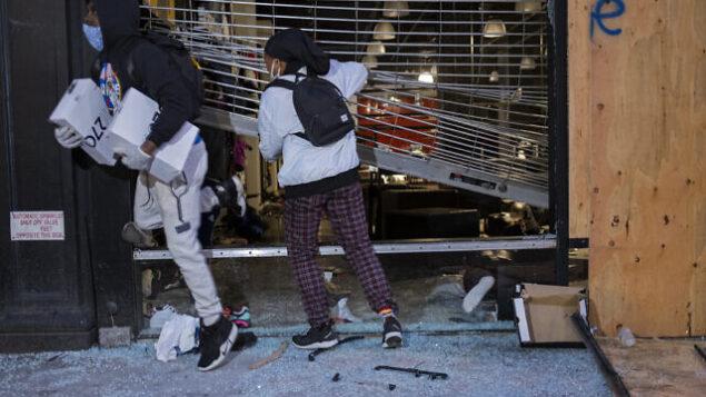 اشخاص يخرجون من متاجر متضررة بعد كسر الزجاج في حي تشيلسي بنيويورك، 1 يونيو 2020. (AP Photo / Craig Ruttle)