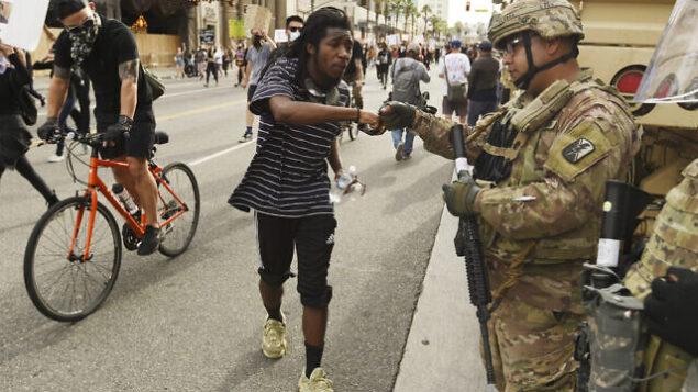 مشارك في مسيرة احتجاجية مع احد عناصر الحرس الوطني في شارع هوليوود، 2 يونيو 2020 ، في لوس أنجلوس. نُظمت احتجاجات في مدن الولايات المتحدة بعد مقتل جورج فلويد، وهو رجل أسود قتل في حجز الشرطة في مينيابوليس في 25 مايو. (AP Photo / Chris Pizzello)