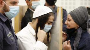 عميرام بن أوليئل (يسار)، الذي أدين بتنفيذ هجوم دوما، يصل إلى جلسة استماع في المحكمة المركزية في اللد، 9 يونيو، 2020. (Tomer Appelbaum/Haaretz/Pool)