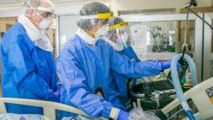 عاملون في المجال الطبي في مستشفى 'إيخيلوف' في تل أبيب يعالجون مريضا في وحدة فيروس كورونا في 4 مايو، 2020.(Yossi Aloni/Flash90)