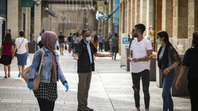 حارس أمن يطلب من الناس وضع أقنعة وجه في مركز ماميلا التجاري بالقرب من البلدة القديمة في القدس، 14 مايو 2020. (Olivier Fitoussi / Flash90)