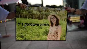 متظاهرتان ضد العنف تحملان صورة لمايا فيشنياك، التي قُتلت في حادثة عنف منزلي، خلال تظاهرة في ميدان هابيما بتل أبيب، 18 مايو، 2020.(Tomer Neuberg/Flash90)