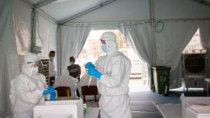 عاملون طبيون في نجمة داوود الحمراء يأخذون عينات لإجراء فحوصات للكشف عن فيروس كورونا في جنوب تل أبيب، 2 يونيو، 2020. (Miriam Alster/Flash90)