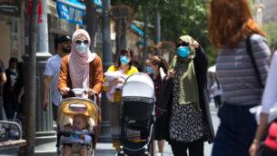 إسرائيليون يرتدون أقنعة وجه يمشون في القدس، 2 يونيو 2020. (Olivier Fitoussi / Flash90)