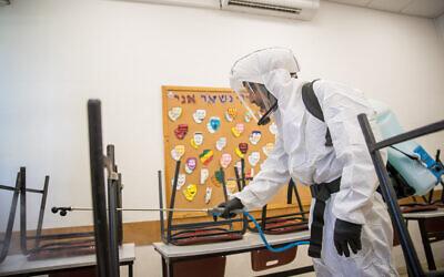عامل نظافة يقوم بتعقيم فصل دراسي في مدرسة 'غيمناسيا رحافيا' في القدس، 3 يونيو، 2020. (Yonatan Sindel/Flash90)