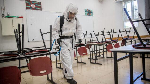 عامل نظافة يقوم بتعقيم فصل دراسي في المدرسة الثانوية 'غيمناسيا رحافيا' في القدس، 3 يونيو، 2020. (Yonatan Sindel/Flash90)