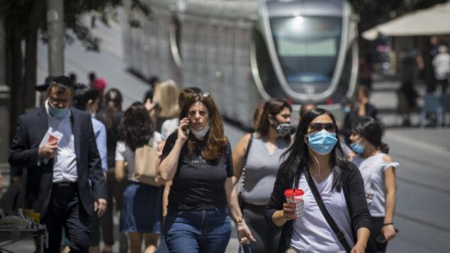 امرأة تستخدم هاتفًا خليويا بينما يرتدي الناس أقنعة الوجه خوفًا من الإصابة بفيروس كورونا في وسط مدينة القدس، 8 يونيو 2020. (Olivier Fitoussi / Flash90)