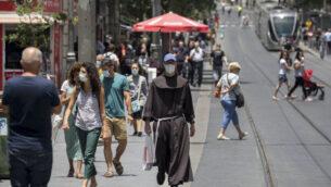 أشخاص يرتدون أقنعة الوجه يمشون في القدس، 8 يونيو 2020. (Olivier Fitoussi / Flash90)