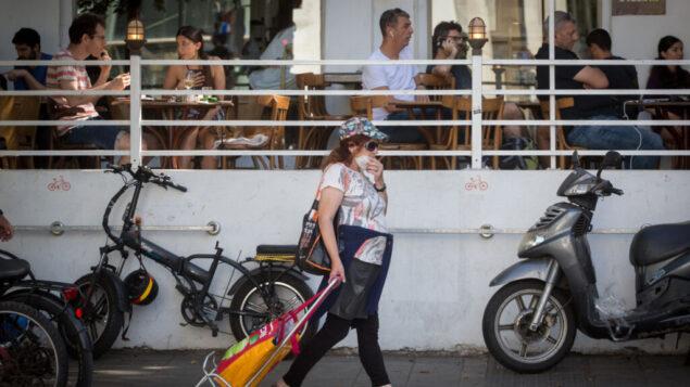 إسرائيليون، بعضهم يرتدون أقنعة واقية، والبعض الآخر كلا، في تل أبيب، 9 يونيو 2020 (Miriam Alster / Flash90)