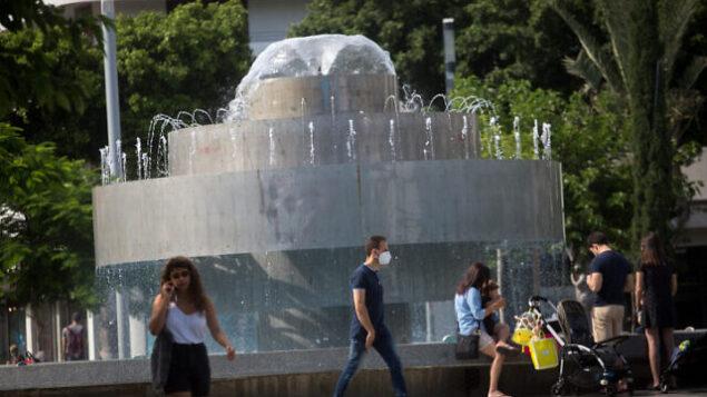 إسرائيليون، بعضهم يضع الكمامات والبعض الآخر لا يضعها، في تل أبيب، 9 يونيو، 2020. (Miriam Alster/Flash90)