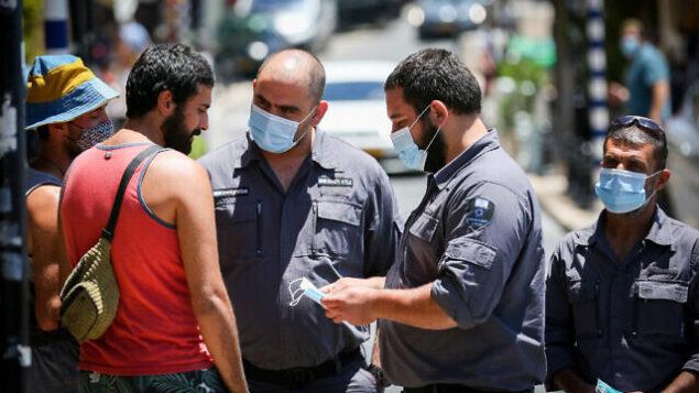 مفتشون يتحدثون مع رجل لا يضع كمامة في مدينة صفد في شمال البلاد، 15 يونيو، 2020 (David Cohen/ Flash90)