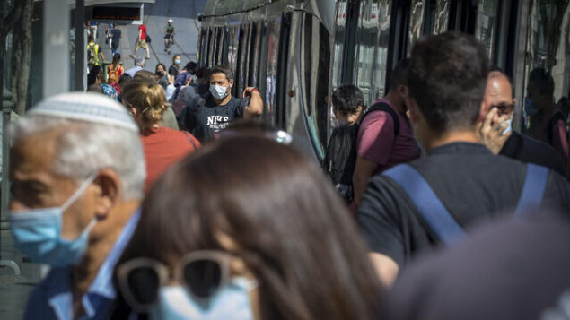 أشخاص يضعون الكمامات في القدس، 16 يونيو، 2020.(Olivier Fitoussi/Flash90)
