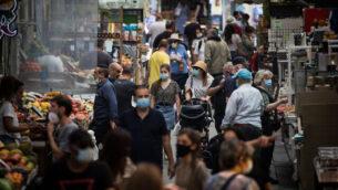 متسوقون في سوق محانيه يهودا في القدس، 17 يونيو، 2020.(Yonatan Sindel/Flash90)