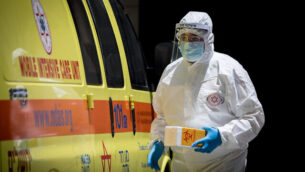 عامل في نجمة داوود الحمراء يصل لإجراء فحص لمريض تظهر عليه أعراض فيروس كورونا في القدس، 23 يونيو، 2020. (Yonatan Sindel/Flash90)