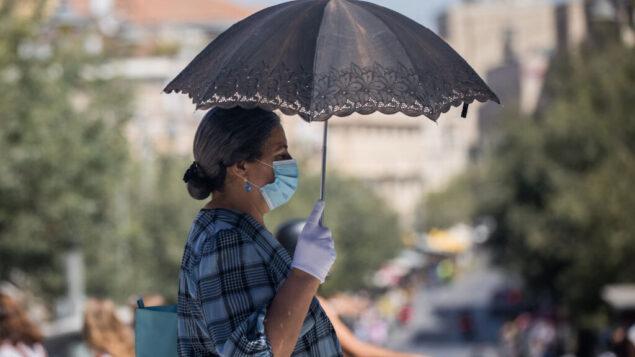 أشخاص يمشون مع أقنعة الوجه في شارع يافا في وسط مدينة القدس، 24 يونيو 2020. (Yonatan Sindel / Flash90)