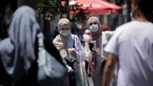 أشخاص يمشون مع أقنعة وجه في شارع يافا في وسط مدينة القدس، 25 يونيو 2020. (Yonatan Sindel / Flash90)