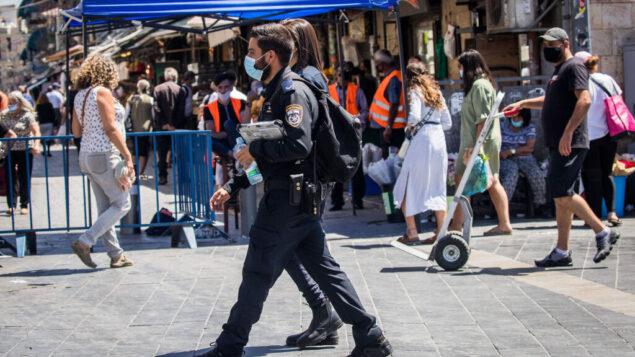 ضباط الشرطة ينفذون قواعد التباعد الاجتماعي خارج سوق محانيه يهودا في القدس، 25 يونيو 2020. (Yonatan Sindel / Flash90)