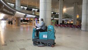 عامل تنظيف في صالة الوصول الخالية في مطار بن غوريون الدولي، 12 يونيو، 2020. (Olivier Fitoussi/Flash90)