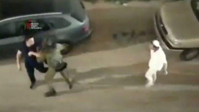جندي إسرائيلي (وسط) يساعد رجلاً فلسطينيًا (يسار) على الفرار من مجموعة من الإسرائيليين الذين هاجموه في مدينة الخليل بالضفة الغربية، 13 يونيو 2020. (Screen capture: Twitter)