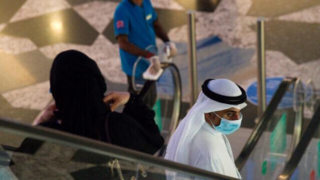 رجل وسيدة إماراتيان في 'مول الإمارات' في دبي، الإمارات العربية المتحدة، مع بدء البلاد بتخفبف القيود المفروضة لمكافحة فيروس كورونا، 27 مايو، 2020.  (AP Photo/Jon Gambrell)