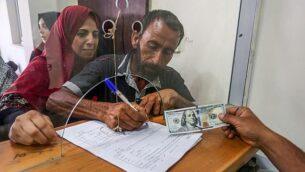 فلسطينيون يستلمون مساعدات مالية من قطر في مكتب بريد بمدينة غزة، 20 يونيو، 2019.  (Abed Rahim Khatib/Flash90)