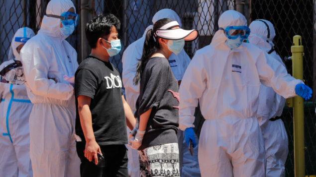 عمال يرتدون سترات واقية يوجهون الناس لإجراء اختبار فيروس في ملعب في بكين، 14 يونيو 2020. (AP / Andy Wong)