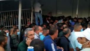 عمال فلسطينيون في طريقهم إلى العمل في إسرائيل، عند حاجز 300 في بيت لحم بالضفة الغربية، يونيو 2020.(Screenshot: Channel 12)