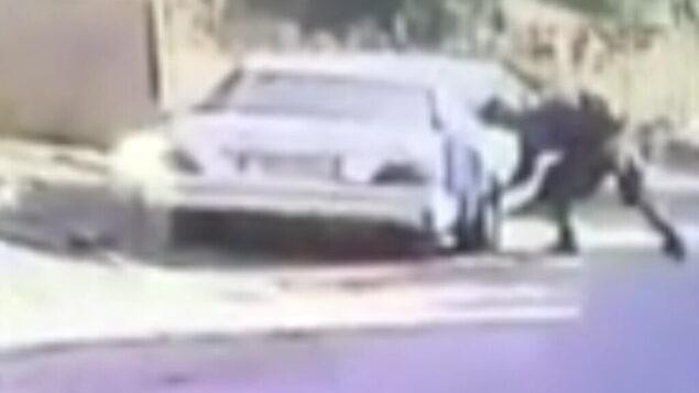 جندي اسرائيلي يقوم على ما يبدو بتمزيق إطارات سيارة ليموزين فلسطينية في قرية كفر قدوم خلال مظاهرة، 30 مايو 2020 (screen capture: B'Tselem)