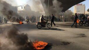 متظاهرون إيرانيون يتظاهرون بين إطارات مشتعلة أثناء مظاهرة ضد ارتفاع أسعار الوقود، في مدينة أصفهان الإيرانية، 16 نوفمبر 2019. (AFP)