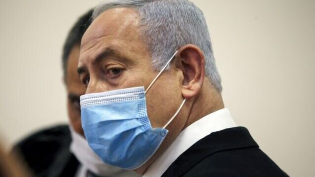 رئيس الوزراء بنيامين نتنياهو وهو يرتدي الكمامة في قاعة المحكمة المركزية في القدس في 24 مايو، 2020، مع انطلاق محاكمته في قضايا فساد.  (Ronen Zvulun / POOL / AFP)