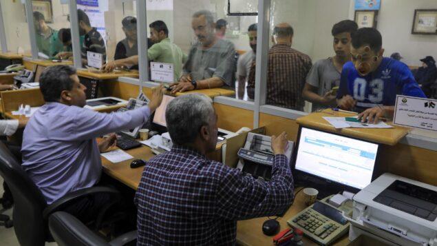 فلسطينيون يتلقون مساعدات مالية من قطر في مكتب بريد في مدينة غزة، 27 يونيو 2020. (Mahmud Hams/AFP)