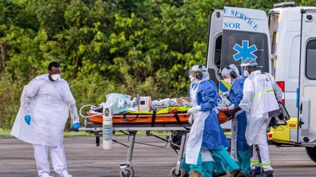 طاقم طبي يحمل مريضًا مصابًا بفيروس كورونا الجديد (كوفيد-19) إلى طائرة إيرباص A400M في قاعدة جويانا الجوية 367 في ماتوري، بالقرب من كايين، في قسم غيانا الفرنسي في الخارج، 28 يونيو 2020 (JODY AMIET / AFP)
