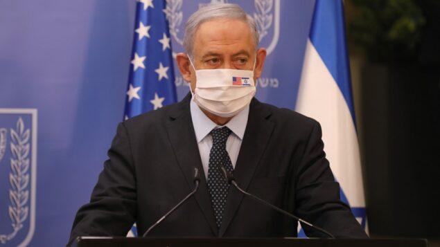 رئيس الوزراء بنيامين نتنياهو يرتدي قناع وجه ضد حماية من كوفيد-19 يحمل العلمين الأمريكي والإسرائيلي، خلال مؤتمر صحفي مع الممثل الأمريكي الخاص لإيران (لا يظهر) في مكتب رئيس الوزراء في القدس، 30 يونيو 2020. (Abir Sultan/POOL/AFP)