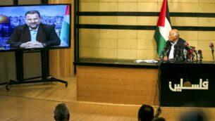 المسؤول الرفيع في فتح جبريل رجوب، في مدينة رام الله بالضفة الغربية، خلال اجتماع عبر الفيديو مع نائب رئيس حماس صالح العاروري (على الشاشة من بيروت) لمناقشة خطة إسرائيل لضم أجزاء من الضفة الغربية، 2 يوليو 2020. (ABBAS MOMANI / AFP)